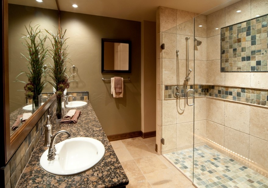 bathroom with double sinks and floor length glass door shower